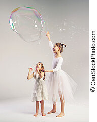 Two sisters with the large soap bubble - Two girls with the...
