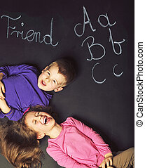 Cute kids playing on the black board - Cute children playing...