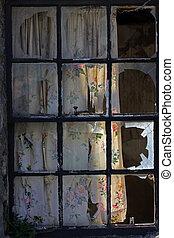 Broken panes - A window with all panes broken by vandals.
