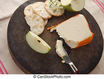 Port Salut cheese, crackers, fruit - cutting board with...