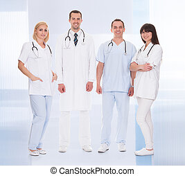 Happy Group Of Doctors Standing Over Blue Background
