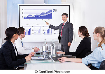 Businessman Explaining Graph - Mature Businessman Explaining...