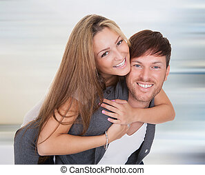 Happy young couple - Young Man Giving Piggyback To His Wife