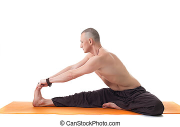 Athletic man with naked torso practicing yoga