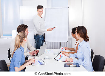 Businessman With Flipchart And Colleagues - Businessman...