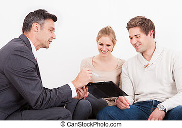 Consultant Showing Clipboard To Couple - Male Consultant...