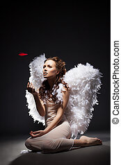 Charming young woman posing dressed as angel