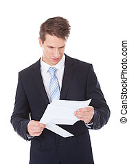 Serious Businessman Reading Document - Portrait Of Serious...