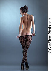Slim woman takes off her tights, back to camera - Slim nude...