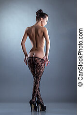 Seductive nude woman posing in translucent tights -...