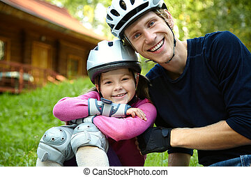 Dad and daughter in a helmet - portrait of a sports dad and...