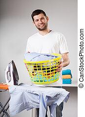 Laundry to ironing - Happy handsome husband doing laundry...
