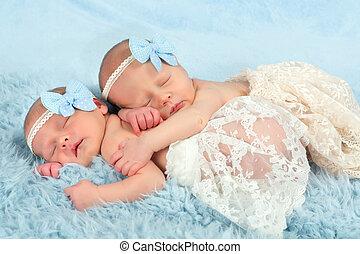 Newborn twin girls - Two adorable newborn twin babies asleep...