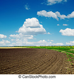 black plowed field and clouds in blue sky