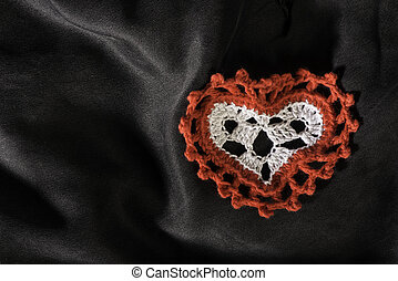 Heart shape made of red textile on black satin