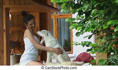 Petting a white dog - Young brunette petting a dog