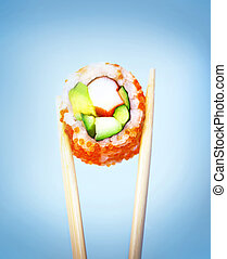 Sushi isolated on blue background, wooden chopsticks holding...