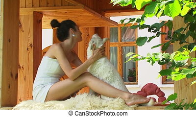 Petting a dog - Young brunette petting a white dog