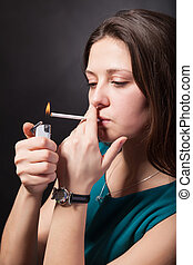 Beautiful young woman is smoking cigarette on black...