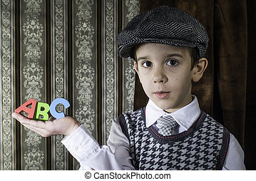 Child in vintage clothes hold letters a b c - Child in...