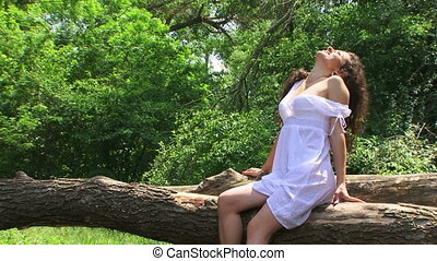 On a tree - Young brunette sitting on a fallen tree