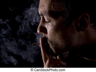 Young man smoking a cigarette on black background