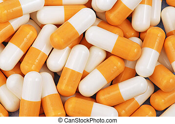Drugs - Yellow and white medical capsules on the one heap