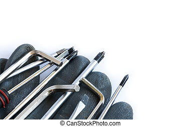 Set of screwdrivers and glove over a white background