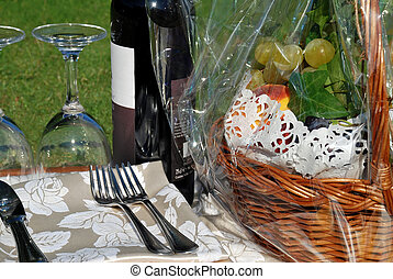 Wine still life on grass with basket of fruits and glasses
