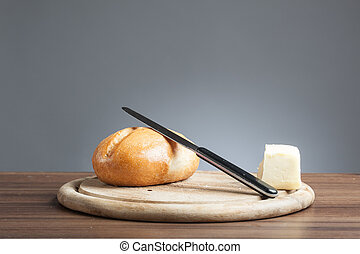 Bread roll, knive, butter, on plate - Breakfast plate with...