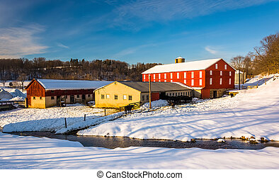 Winter view of a red barn and a stream in Seven Valleys,...
