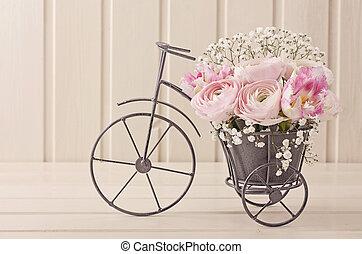 Ranunculus flowers in a bicycle vase