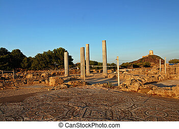 Ruins and lighthouse - Ancient Sardinian ruins of Nora with...