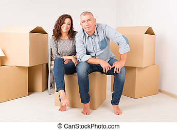 Couple at new home - Happy mature couple unpacking boxes in...
