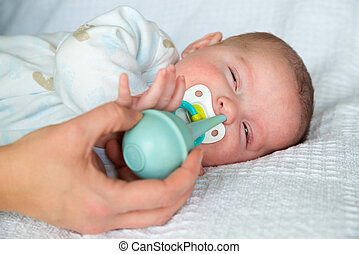 Bulb syringe to clean baby's nose - Mother using bulb...