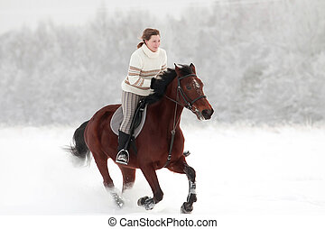 Winter riding - Young woman on horseback at winter day
