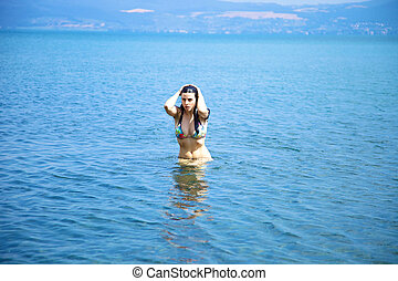 Beautiful woman getting out of the water in lake