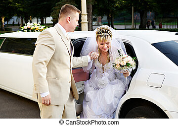 Happy bride and groom out of wedding limousine