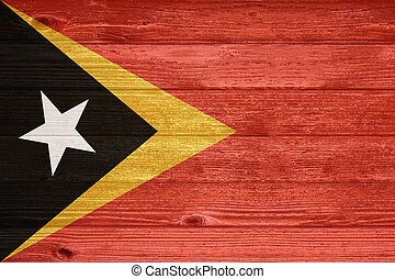 East Timor Flag painted on old wood plank background. - East...