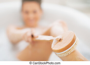 Closeup on young woman in bathtub using body brush