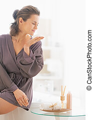 Young woman smelling soap