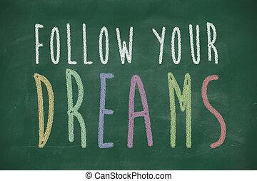 follow your dreams phrase handwritten on blackboard