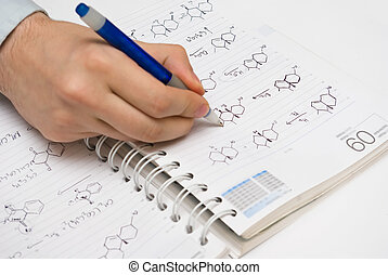 student drawing structural formulas in a chemistry notebook