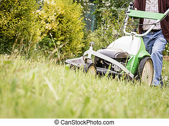 Senior man mowing the lawn with a lawnmower machine