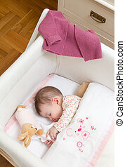 Baby girl sleeping in a cot with pacifier and toy - Portrait...