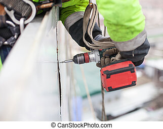 Closeup of industrial climber with screwdriver on metal...