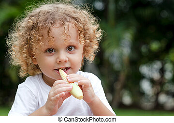 Happy little boy holding a corn. Concept of healthy food.