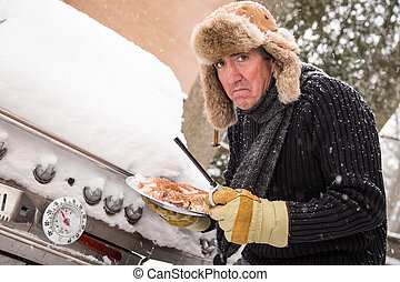 Miserable winter barbequer - Snow continues to fall on a...