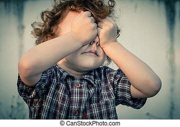 crying little boy covers his face