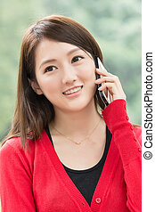 Smiling Asian young woman take a call, closeup portrait in...